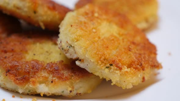 In vegetable oil deep fried fish burger pieces close-up 4K 2160p 30fps UltraHD tilting video - Fried
