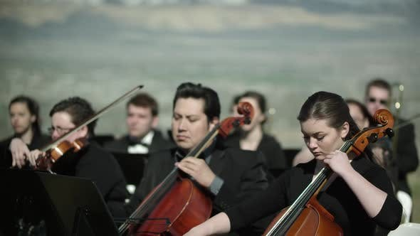 Shot of outdoor orchestra, close up on the musicians playing string instruments