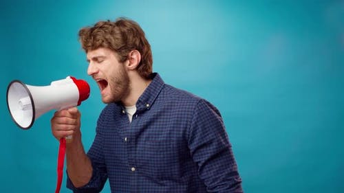 Irritated Bearded Young Man Screaming in Megaphone Against Blue Background