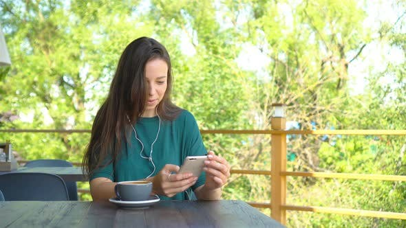 Thumbnail for Woman with Smartphone in Cafe Drinking Coffee Smiling and Texting on Mobile Phone. Portrait of