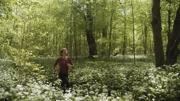 Peaceful and Lush Green Forest with Woman Taking a Rest From Jogging