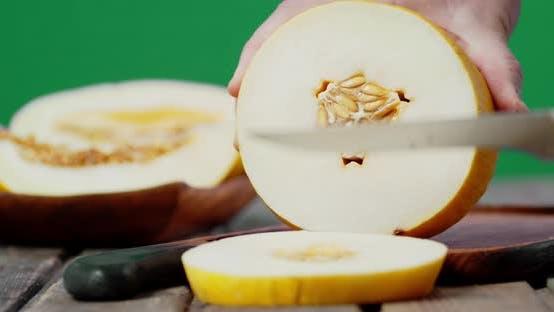 Male Hands Slicing a Ripe Melon Into Round Slices.