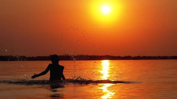 Thumbnail for Silhouette of Boy at Sunset Raises Hands and Creating Splashes of Water