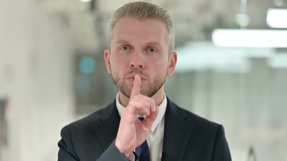 Thumbnail for Portrait of Serious Businessman Putting Finger on Lips