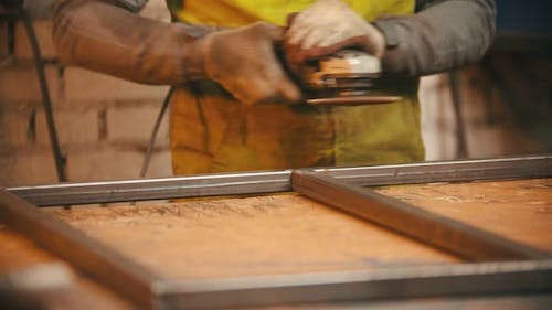 Man Worker Grinding the Seams of an Iron Frame