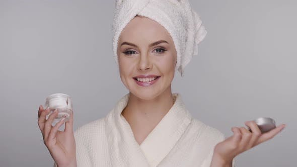 Thumbnail for Happy Woman in Robe and Towel on Head Apllying Cream on Her Face