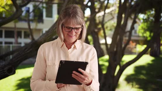 Happy older woman playing with portable tablet computer outdoors in public park