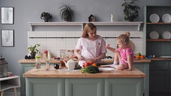 Thumbnail for Beautiful Mother Cooking Dinner on Kitchen with Little Kid