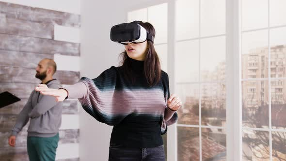 Cover Image for Female Architect Using Virtual Reality Goggles in Empty Apartment