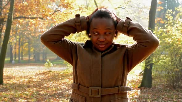 Thumbnail for A Young Beautiful African Girl Stands in the Woods and Gives Her Loose Hair Into a Ponytail