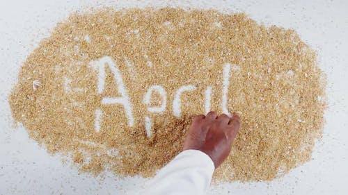Hand schreibt auf Sand April