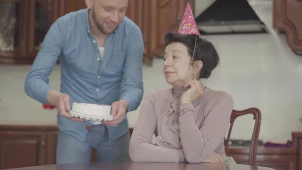 Thumbnail for Mature Lady Sitting at the Table with Birthday Cap on Her Head. Adult Grandson Brings the Small Cake
