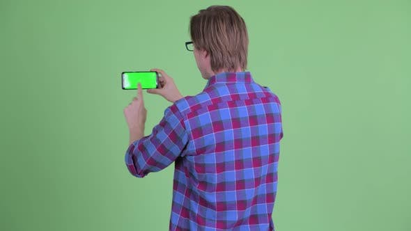 Cover Image for Rear View of Young Hipster Man Taking Picture with Phone