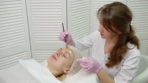 A Young Woman Gets A Procedure From A Beautician.Cosmetologist Making Cosmetic Facial White Mask