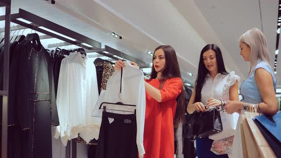 Girl Chooses Clothes and a Woman's Handbag in the Store and Consults with Her Friends