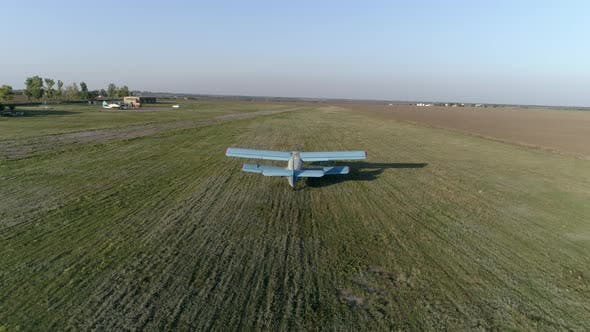 Thumbnail for Blue Aircraft Takes Off Over Field Against Sky and Horizon Line in Spring