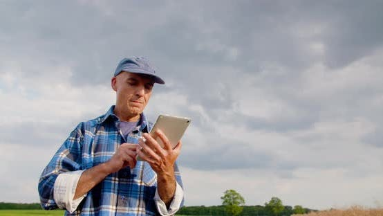 Thumbnail for Farmer Using Digital Tablet at Farm Against Blue Sky and Clouds