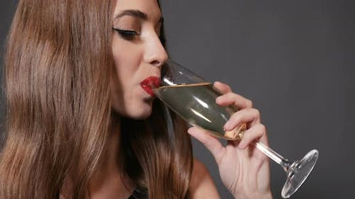 Woman Drinks Champagne at New Year Party
