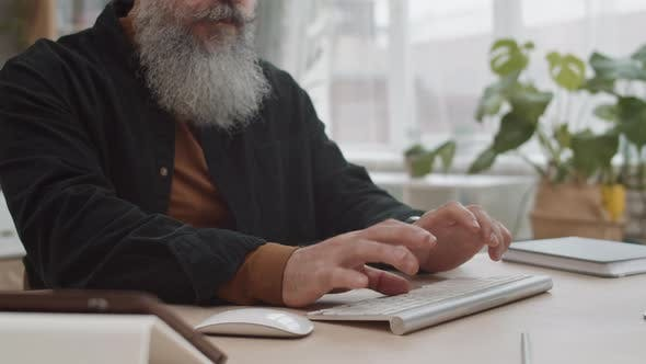 Thumbnail for Unrecognizable Bearded Person Typing on Keyboard