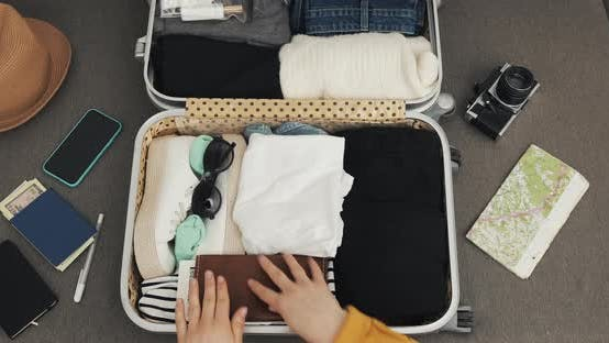 Thumbnail for Woman's Hands Packing Suitcase for a Journey on the Bed at Home