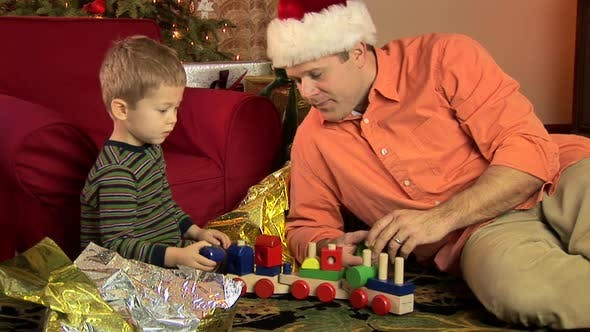 Thumbnail for Father and little boy playing with train by Christmas tree