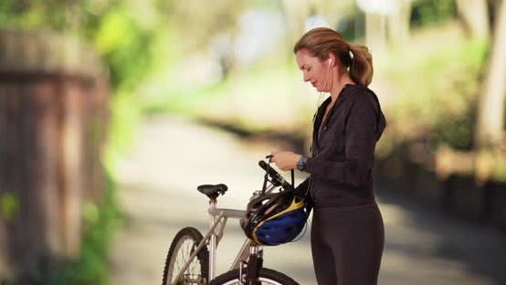 Thumbnail for Woman putting on helmet, going for bike ride on sunny day in the park