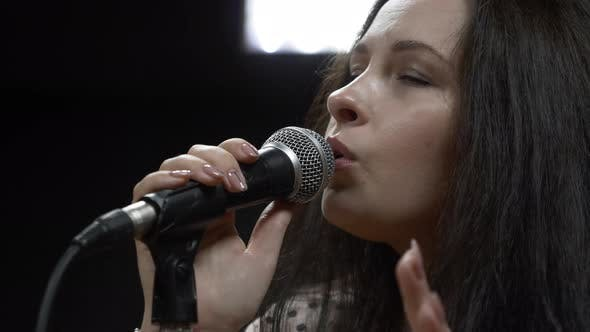 Young brunette woman with microphone is emotionally singing song in professional recording studio.
