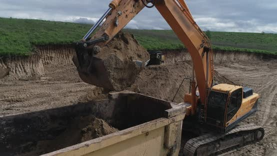 Thumbnail for A Crawler Tractor Fills The Ground With A Bucket Into A Truck