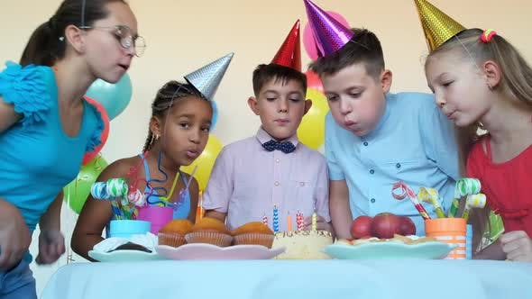 Children with Party Cones Blow Out Burning Candles