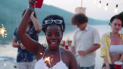 Joyous Black Woman Dancing with Sparkler at Lake Party
