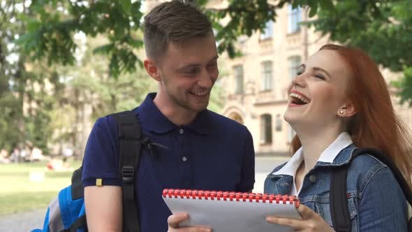 Thumbnail for Female Student Asks Her Classmate About Something in Notebook on Campus