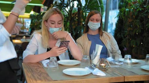 Restaurant-Besucher in sterilen Gesichtsmasken auf der Terrasse