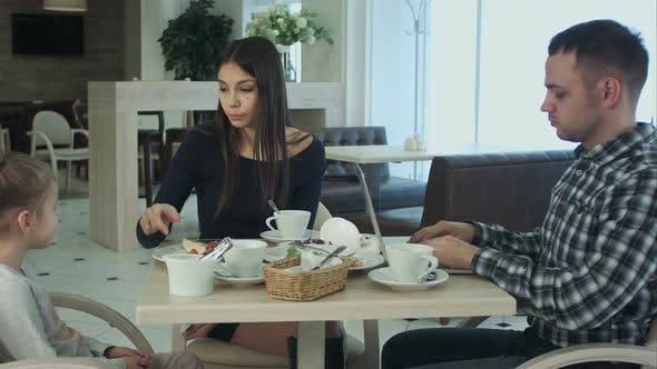 Thumbnail for Father Using His Laptop While Sitting with His Wife and Daughter in Cafe