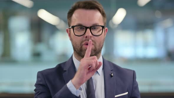 Middle Aged Businessman Showing Quiet Sign Finger on Lips
