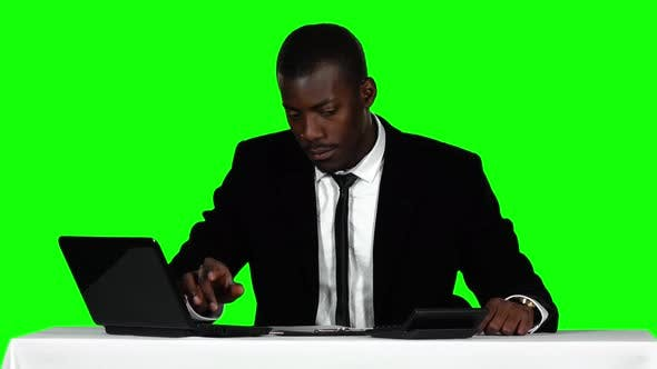 Cover Image for Businessman Uses the Calculator and a Laptop. Green Screen