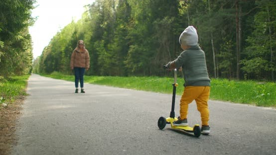 Thumbnail for Young Mother Showing Her Toddler Son How To Ride a Scooter in a Park