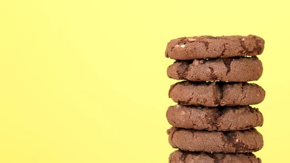 Thumbnail for Stack of Oatmeal Cookies with Cocoa Chocolate and Hazelnuts Rotating on Yellow Background