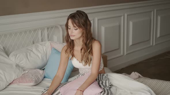 A Young Woman Sits on a Soft Bed in the Bedroom and Holds a Cup of Coffee in Her Hands. A Girl in
