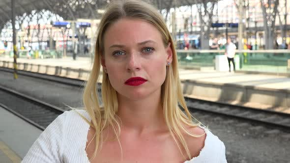 Thumbnail for A Young Beautiful Woman Looks at the Camera on a Train Station Platform - Closeup