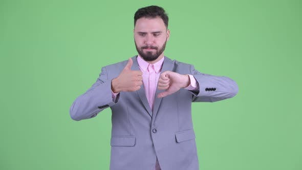 Cover Image for Confused Young Bearded Businessman Choosing Between Thumbs Up and Thumbs Down