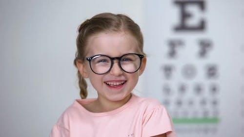 Joyous Little Girl in Eyeglasses Laughing