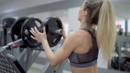 Beautiful muscular girl is getting ready to perform a barbell exercise