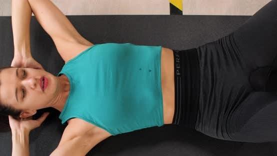 Fitness Frau Training Bauchmuskelübungen auf der Etage Draufsicht. Spotswoman Training Bauchmuskeln liegend