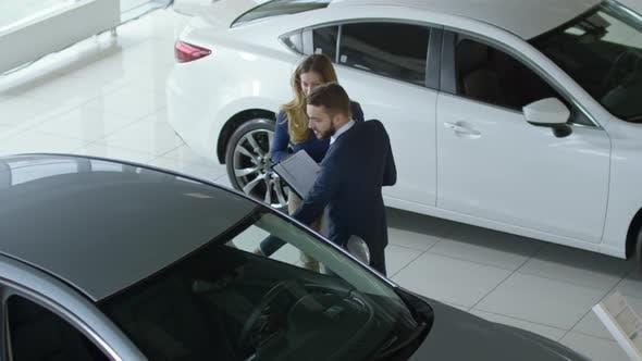 Thumbnail for Salesman Showing Car to Female Client at Dealership