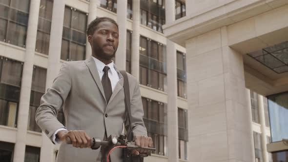 Thumbnail for Young Businessman Riding E Scooter in City