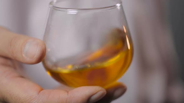 Thumbnail for Male Hand Shaking a Glass With Tasty Bourbon Before Trying It, Super Close-Up