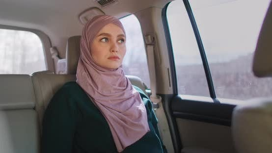 Thumbnail for A Serious, Thoughtful Arab Woman in a Car in the Passenger Seat. Rides in the Car and Looks Out the