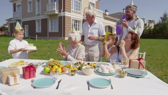 Thumbnail for Little Boy Bringing Birthday Cake to Grandmother on Family Dinner