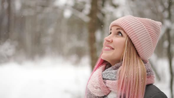 Cover Image for Woman in a Jacket and Hat in Slow Motion Looks at the Snow and Catches Snowflakes Smiling