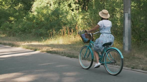 Smiling female is pedaling on bike. Cyclist girl in dress rides vintage bicycle. Woman cycling